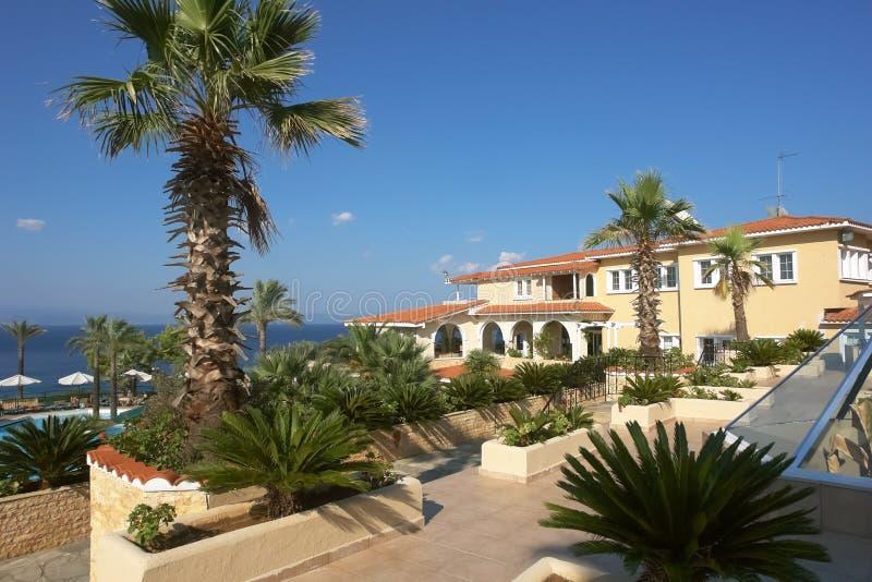Άποψη του κίτρινου κτηρίου, της μπλε θάλασσας και των πράσινων φοινίκων στο ξενοδοχείο, Ελλάδα στοκ εικόνες