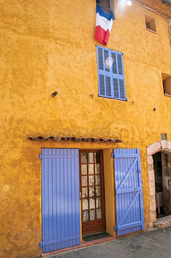 Άποψη του κίτρινου σπιτιού με τους μπλε τυφλούς και της σημαίας στον sillans-Λα-καταρράκτη στοκ εικόνα