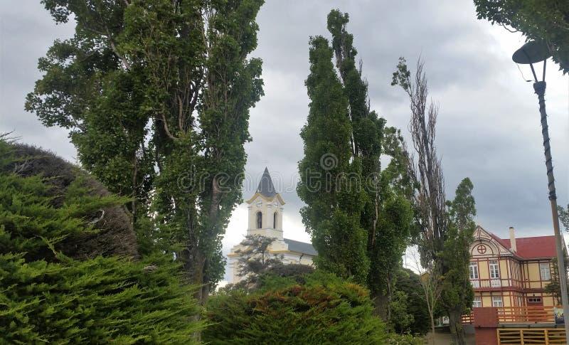 Άποψη του καμπαναριού εκκλησιών και του κτηρίου tudor-ύφους με το διακοσμητικό μισό-εφοδιασμό με ξύλα και evergreens σε Puerto Na στοκ εικόνες