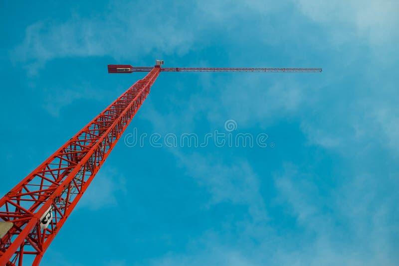 Άποψη του κόκκινου γερανού κατασκευής στο μπλε ουρανό στοκ φωτογραφία με δικαίωμα ελεύθερης χρήσης