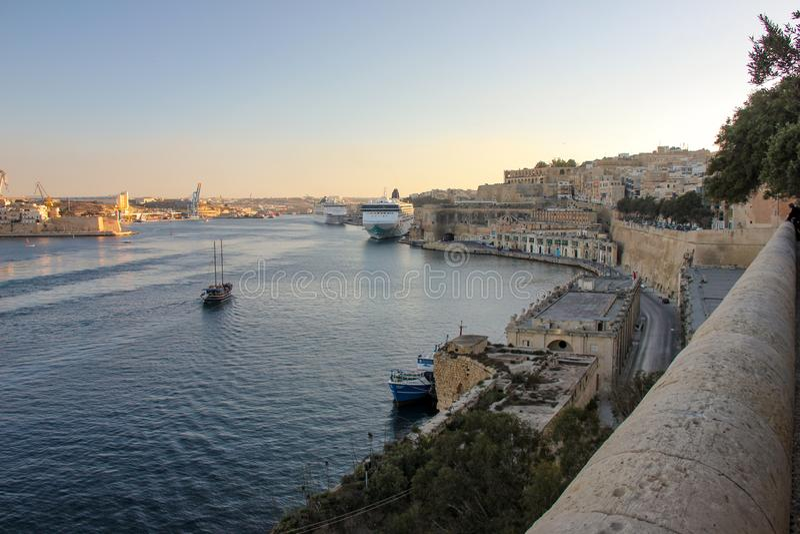 Άποψη του μεγάλου λιμανιού σε Valletta κατά τη διάρκεια του ηλιοβασιλέματος Τρεις πόλεις και μεγάλα σκάφη της γραμμής κρουαζιέρας στοκ εικόνες