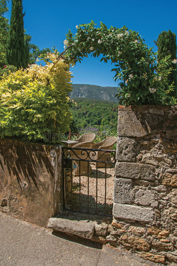 Άποψη του μικρού κήπου πίσω από την πύλη σιδήρου και του τοίχου πετρών στο χωριό Ménerbes στοκ εικόνα