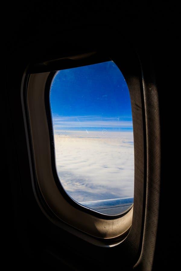 Άποψη του μπλε ουρανού με τα άσπρα σύννεφα μέσω του πετώντας αεροπλάνου παραθύρων παραφωτίδων στοκ εικόνες