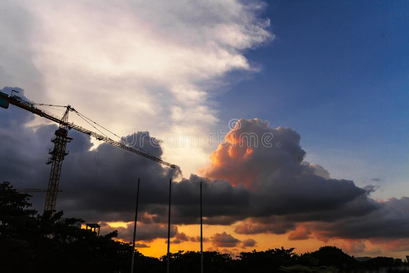 Άποψη του νεφελώδους ουρανού στο σούρουπο με τη σκιαγραφία πρώτου πλάνου γερανού κατασκευής και τριών κονταριών σημαίας στοκ εικόνες με δικαίωμα ελεύθερης χρήσης