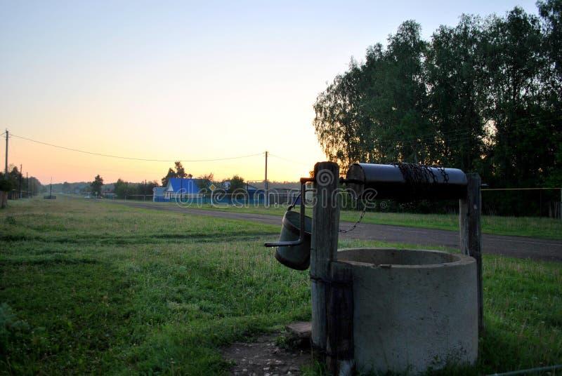 Άποψη του παλαιού καλά και της του χωριού οδού το πρωί αρχών του καλοκαιριού στοκ εικόνες με δικαίωμα ελεύθερης χρήσης