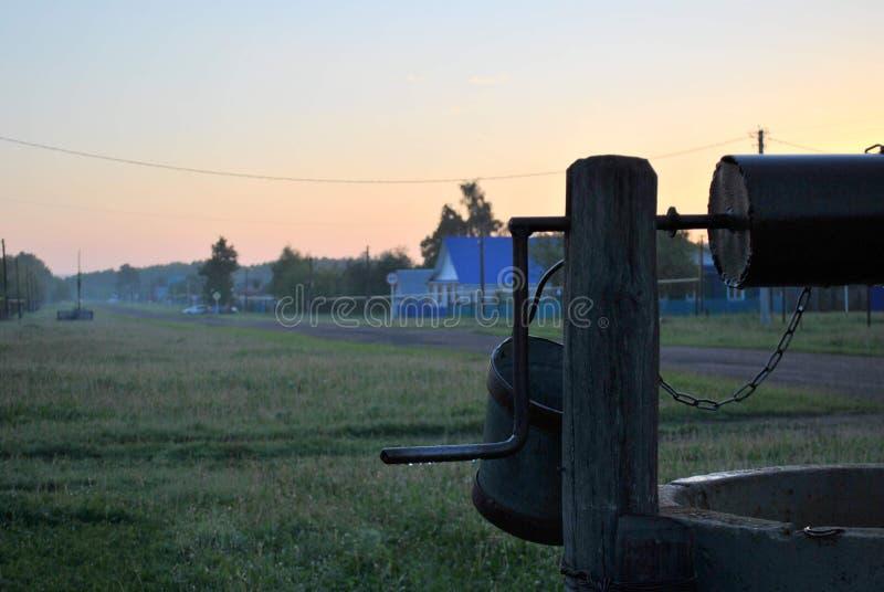 Άποψη του παλαιού καλά και της του χωριού οδού το πρωί αρχών του καλοκαιριού στοκ εικόνες