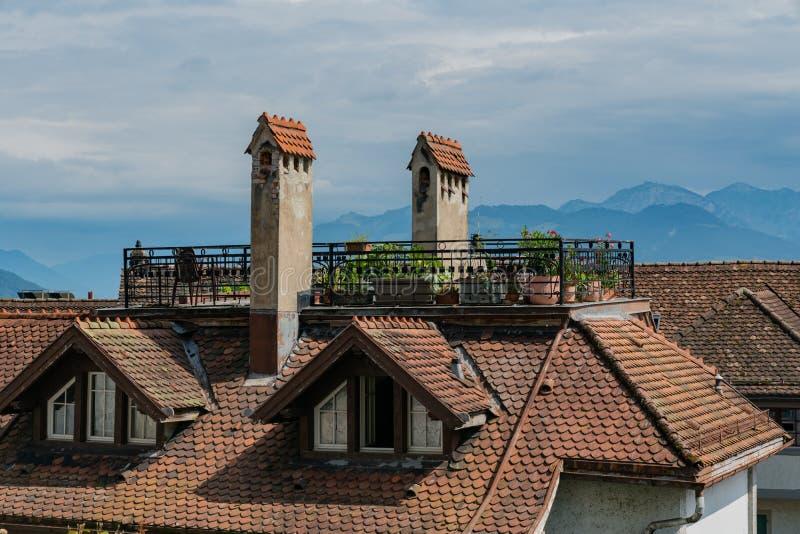 Άποψη του παλαιού σπιτιού με ένα πεζούλι στεγών και του κήπου στην Ευρώπη με το τοπίο βουνών πίσω στοκ εικόνα
