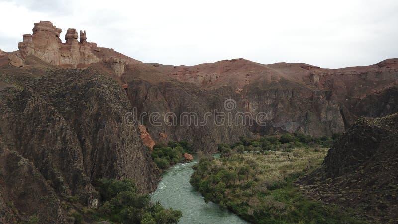Άποψη του ποταμού και του φαραγγιού Charyn Οι δύσκολοι απότομοι βράχοι και τα γκρίζα σύννεφα στοκ εικόνα