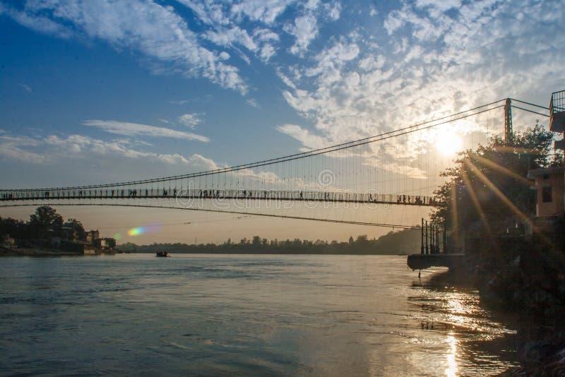 Άποψη του ποταμού Ganga και της γέφυρας Jhula κριού στο ηλιοβασίλεμα Rishikesh Ινδία στοκ εικόνες