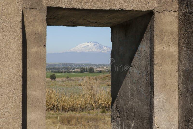 Άποψη του υποστηρίγματος Etna από ένα εγκαταλειμμένο παράθυρο στην επαρχία στοκ εικόνα