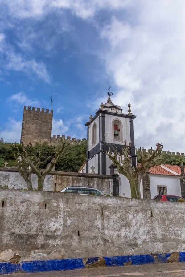 """Άποψη του φρουρίου και του ρωμαϊκού κάστρου Luso Ã""""bidos, της καθολικών εκκλησίας και του ουρανού με τα σύννεφα, στην Πορτογαλ στοκ φωτογραφία με δικαίωμα ελεύθερης χρήσης"""
