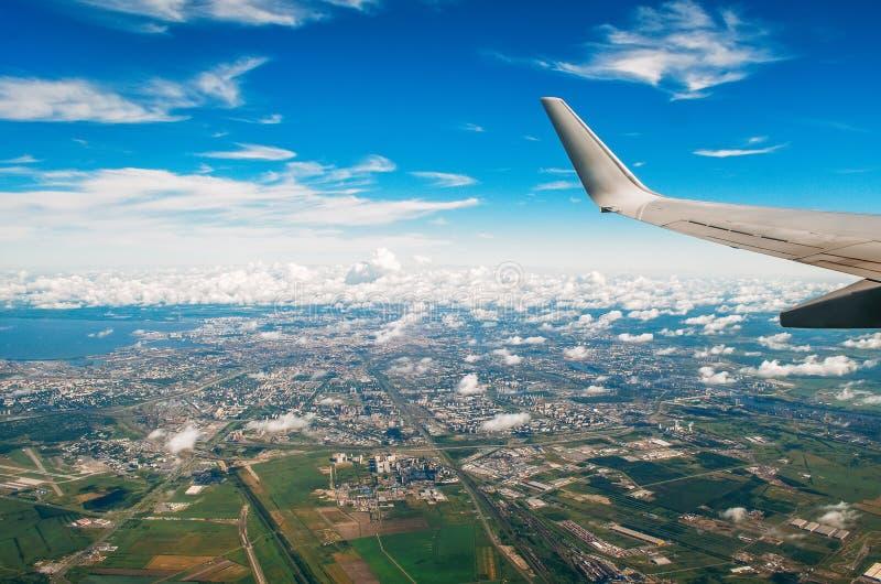 Άποψη του φτερού του αεροπλάνου στην παραφωτίδα στην πόλη και τον αερολιμένα με τα γραφικά σύννεφα στοκ εικόνα