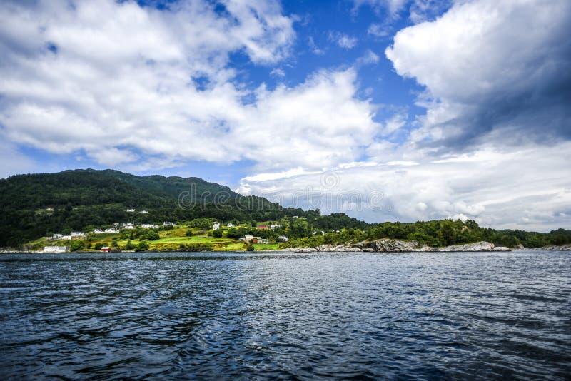 Άποψη του λόφου με τα σπίτια από την ακτή της Νορβηγίας με το beauti στοκ φωτογραφίες