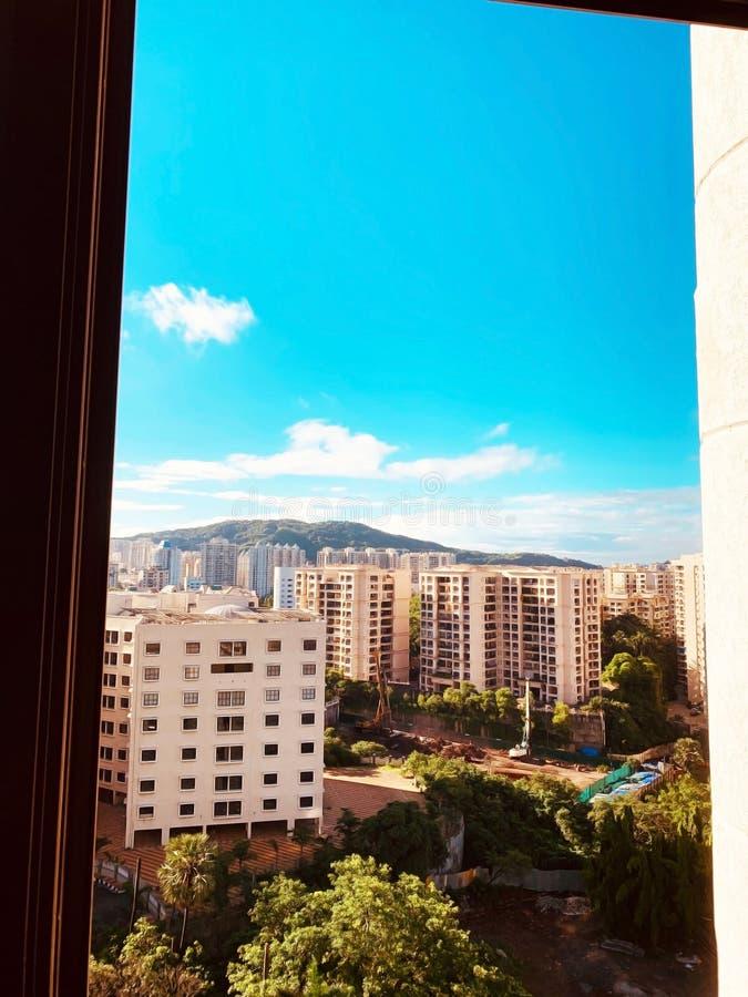 Άποψη των διαμερισμάτων, των δέντρων, των λόφων και του μπλε ουρανού με τα μερικά σύννεφα από ένα παράθυρο μια ηλιόλουστη ημέρα στοκ εικόνες