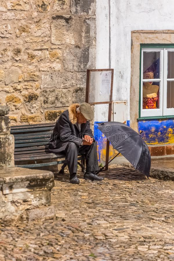 Άποψη των ηλικιωμένων με το χαρακτηριστικό παλτό, που κάθεται στον ξύλινο πάγκο, με το καπέλο βροχής ανοικτό στο έδαφος, στο τετρ στοκ φωτογραφία
