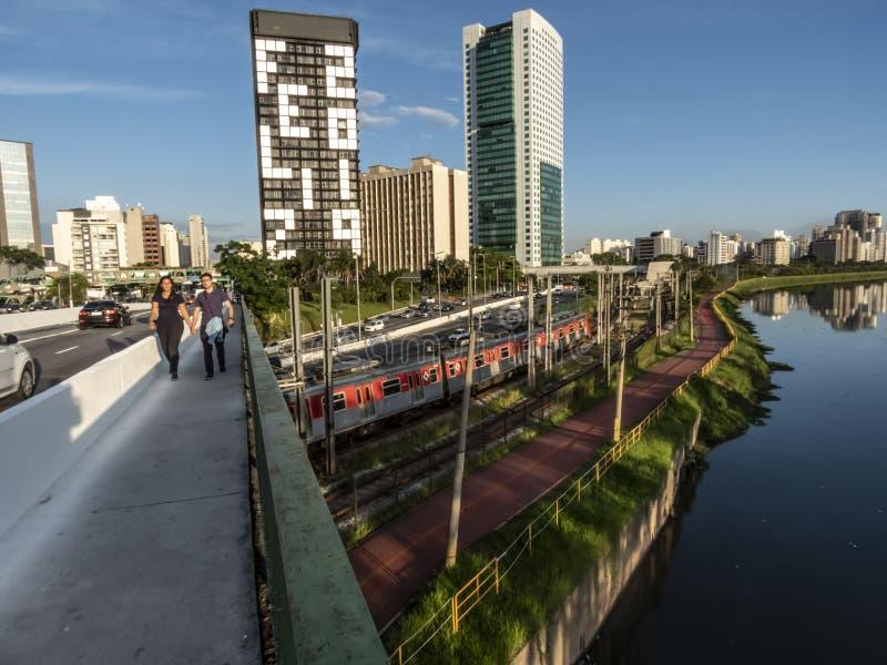 Άποψη των κτηρίων, τραίνο CPTM, κυκλοφορία των οχημάτων και ποταμός στην οριακή λεωφόρο ποταμών Pinheiros στοκ εικόνες