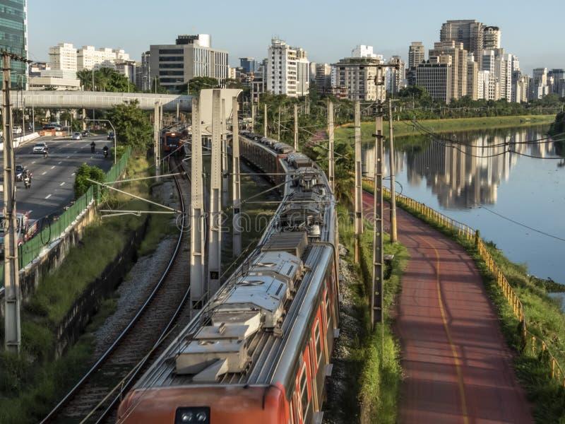 Άποψη των κτηρίων, τραίνο CPTM, κυκλοφορία των οχημάτων και ποταμός στην οριακή λεωφόρο ποταμών Pinheiros στοκ φωτογραφία