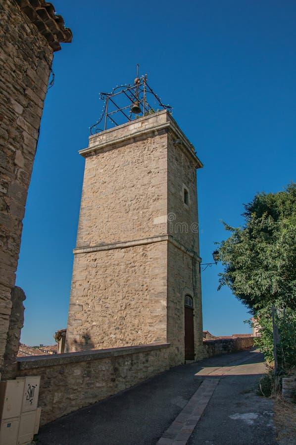 Άποψη των παραδοσιακών σπιτιών πετρών και του πύργου φυσητήρων σε μια οδό στην ανατολή, σε châteauneuf-de-Gadagne στοκ εικόνες