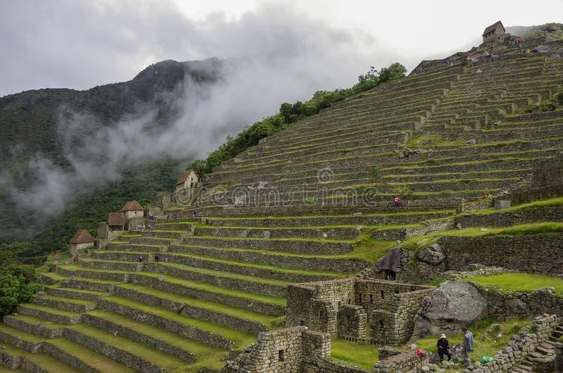 Άποψη των πεζουλιών της χαμένης πόλης Inca Machu Picchu σύννεφα χαμηλά στοκ φωτογραφία με δικαίωμα ελεύθερης χρήσης