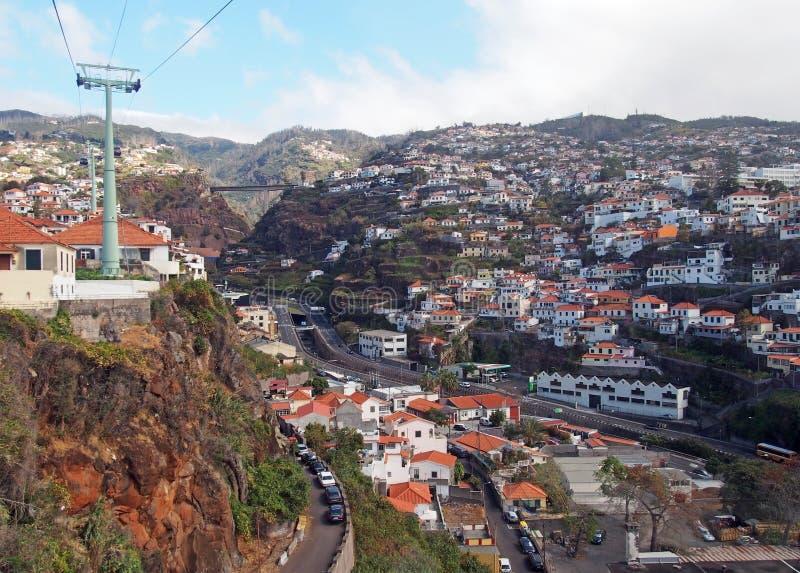 Άποψη των σπιτιών και των οδών του Φουνκάλ από το τελεφερίκ που δημιουργεί το βουνό στο monte με την οδικά γέφυρα και τα βουνά στοκ εικόνα με δικαίωμα ελεύθερης χρήσης