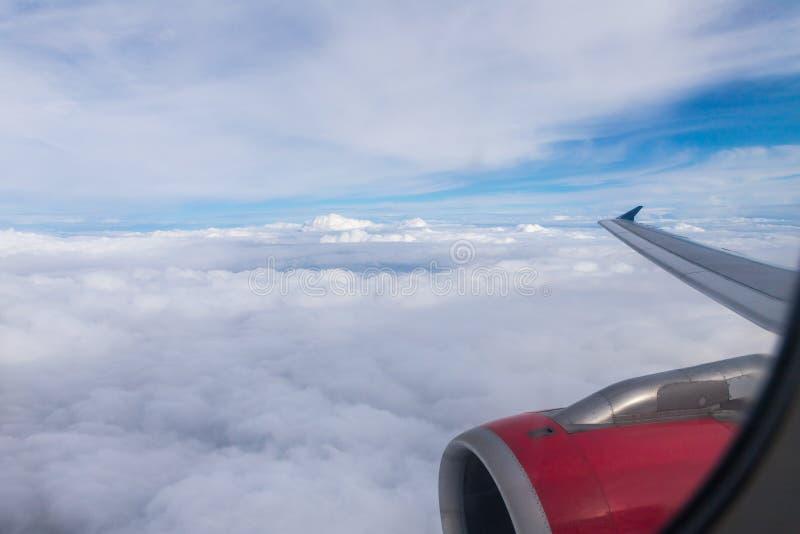 Άποψη των σύννεφων, του φτερού των αεροσκαφών και της μηχανής των αεροσκαφών από το παράθυρο ενός πετώντας αεροπλάνου στοκ εικόνες
