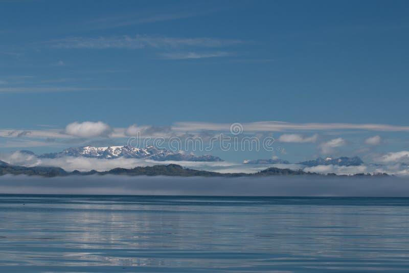 Άποψη των χιονοσκεπών βουνών και των χαμηλών άσπρων σύννεφων πριν από το μπλε ουρανό και απεικόνιση της ήρεμης θάλασσας του Καναδ στοκ φωτογραφία με δικαίωμα ελεύθερης χρήσης