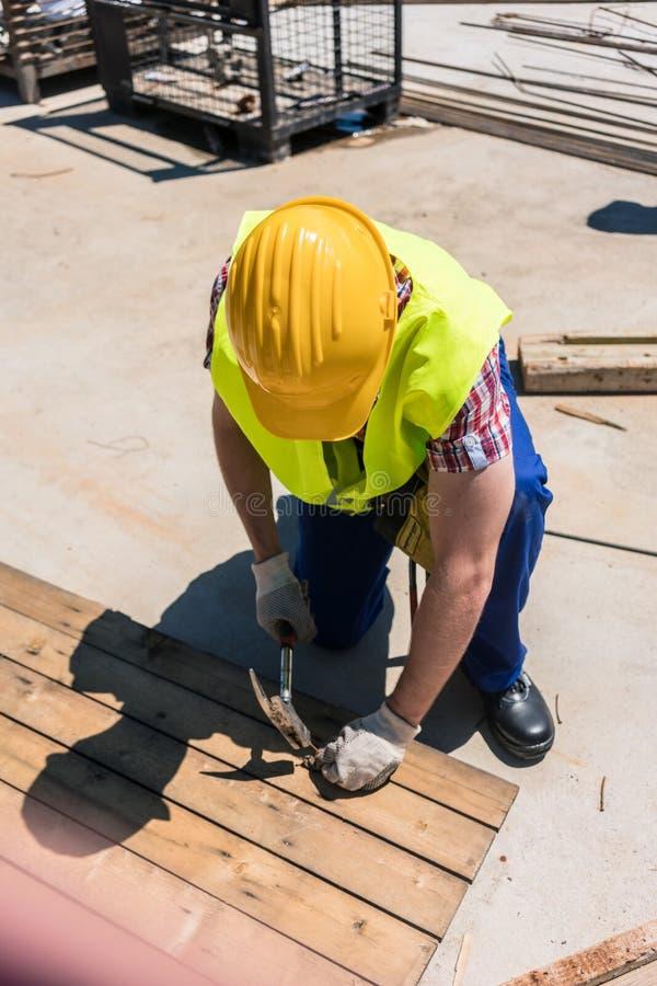 Άποψη υψηλός-γωνίας ενός χειροποίητου εργαζομένου που χρησιμοποιεί ένα σφυρί στοκ εικόνες με δικαίωμα ελεύθερης χρήσης