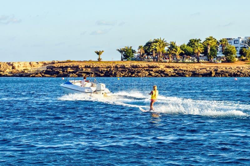 Άποψη φωτός της ημέρας κάνοντας σκι αναβάτη νερού ατόμων στο ρυθμίζοντας από τη βάρκα στοκ εικόνα με δικαίωμα ελεύθερης χρήσης