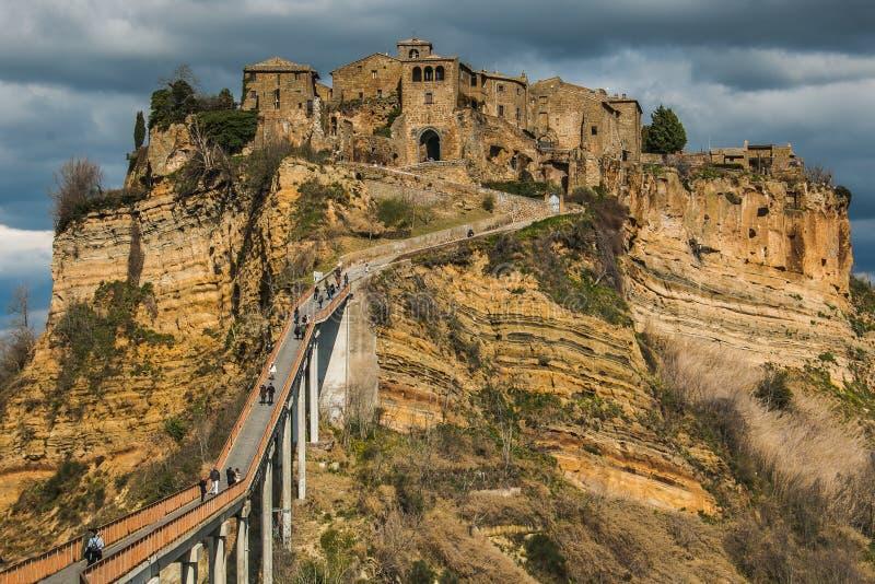 Άποψη Civita Di Bagnoregio ` η πόλη που πεθαίνει ` με τους τουρίστες που περπατούν στη γέφυρα που επισκέπτεται στοκ εικόνα