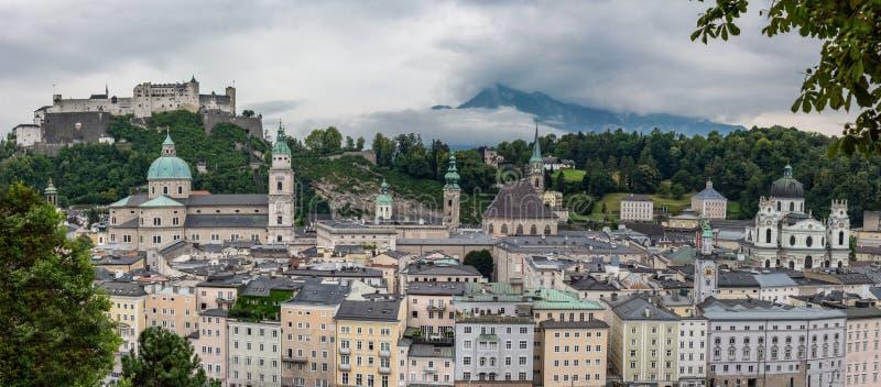 Άποψη Façade και Hohensalzburg το μεσαιωνικό Castle πόλεων του Σάλτζμπουργκ με το νεφελώδες υπόβαθρο Άλπεων και τους πράσινους δ στοκ εικόνες