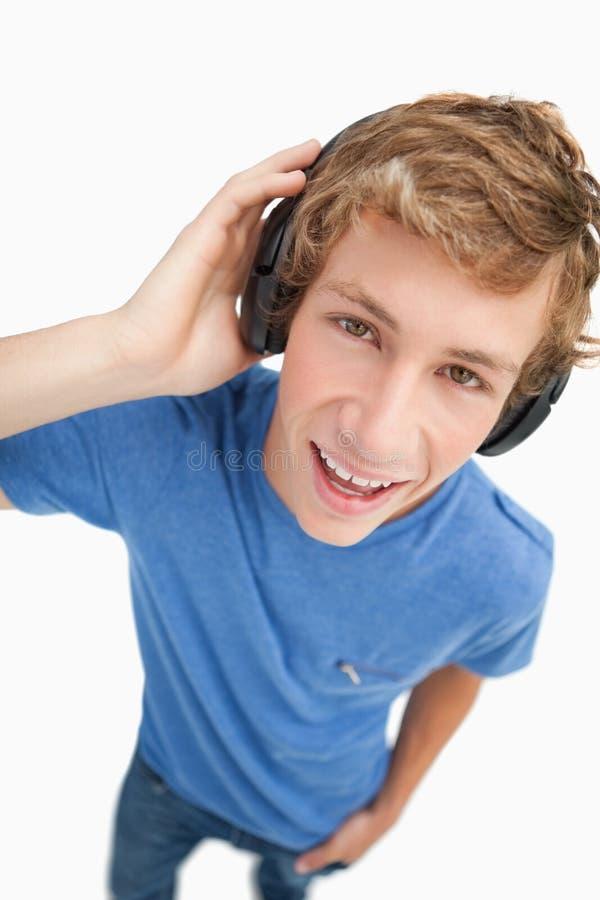 Άποψη Fisheye ενός ξανθού σπουδαστή που φορά τα ακουστικά στοκ εικόνες