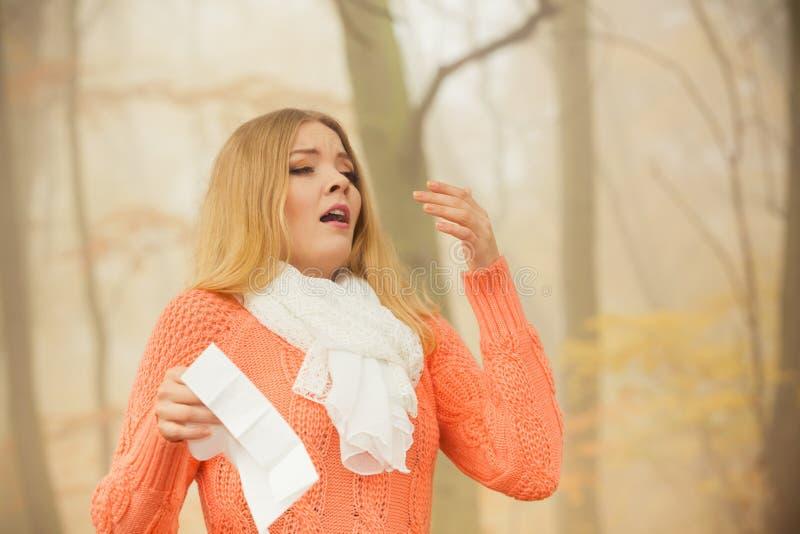 Άρρωστη άρρωστη γυναίκα στο πάρκο φθινοπώρου που φτερνίζεται στον ιστό στοκ εικόνα
