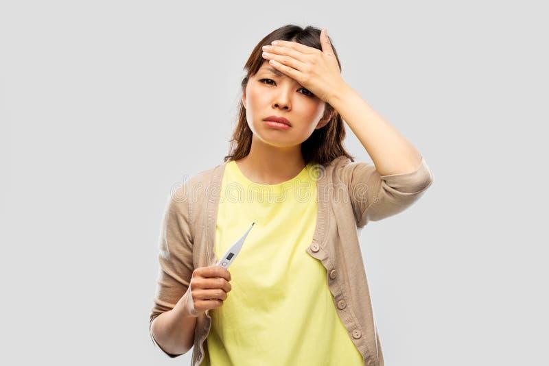 Άρρωστη ασιατική γυναίκα με το θερμόμετρο που έχει τον πυρετό στοκ εικόνα με δικαίωμα ελεύθερης χρήσης