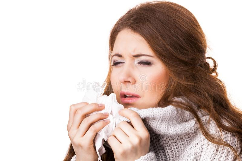 Άρρωστη γυναίκα παγώματος που φτερνίζεται στον ιστό στοκ εικόνες