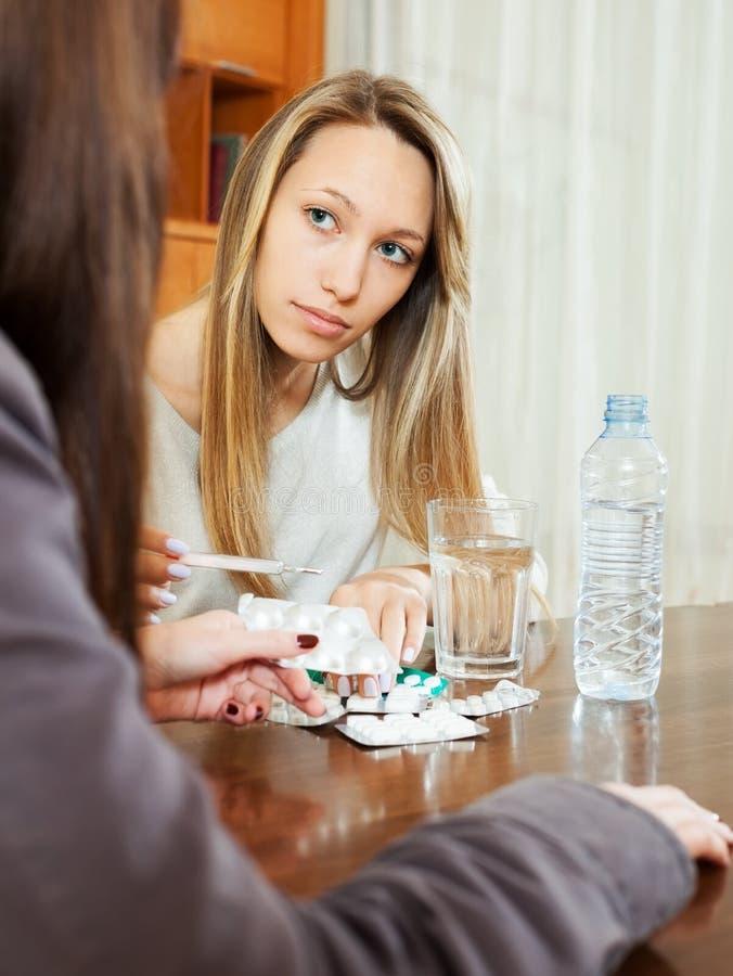 Άρρωστη γυναίκα που κοιτάζει από το θερμόμετρο στο σπίτι στοκ εικόνα με δικαίωμα ελεύθερης χρήσης