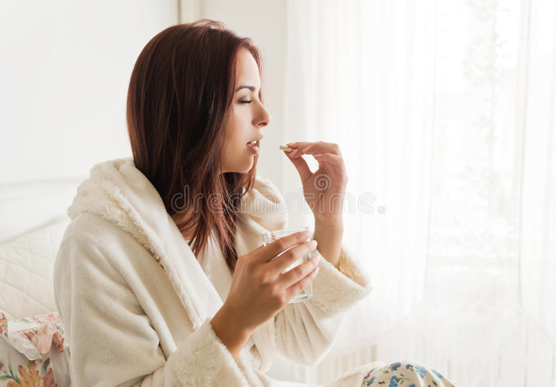 Άρρωστη γυναίκα που κρατά ένα ποτήρι του νερού, που παίρνει τα χάπια στοκ εικόνα με δικαίωμα ελεύθερης χρήσης