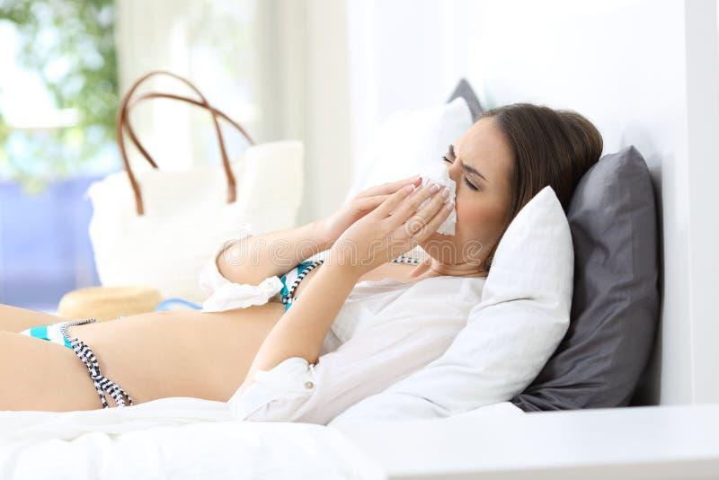 Άρρωστη γυναίκα που φτερνίζεται σε ένα ξενοδοχείο στις διακοπές στοκ εικόνες με δικαίωμα ελεύθερης χρήσης