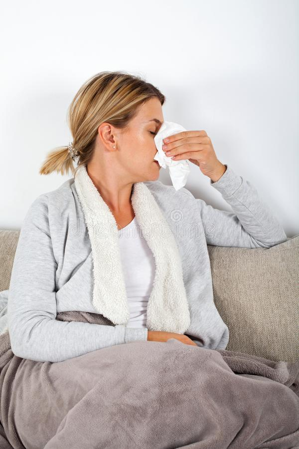 Άρρωστη γυναίκα που φυσά τη μύτη της στοκ φωτογραφία