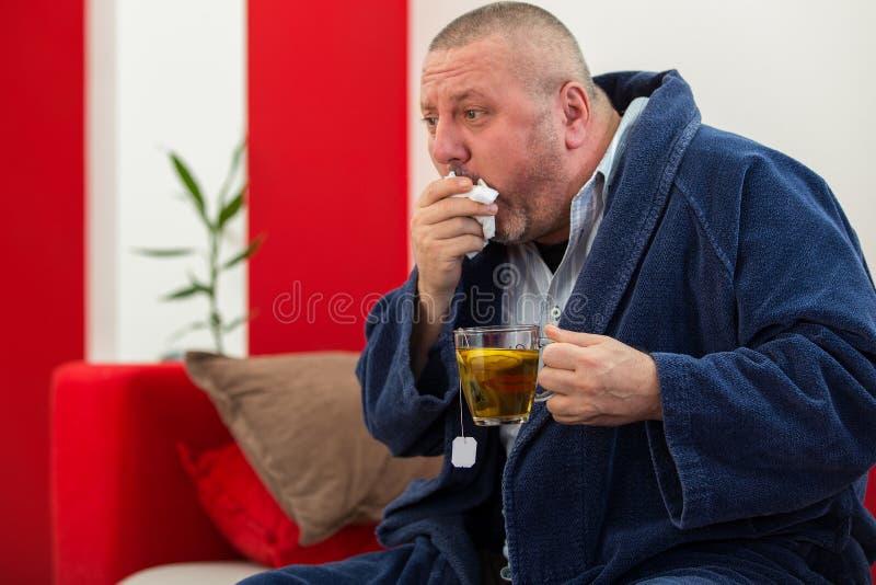 Άρρωστος άνδρας που φυσά τη μύτη του με την πετσέτα εγγράφου και που πίνει το τσάι στο σπίτι στοκ φωτογραφίες