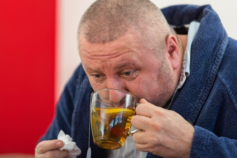 Άρρωστος άνδρας που φυσά τη μύτη του με την πετσέτα εγγράφου και που πίνει το τσάι στο σπίτι στοκ εικόνα