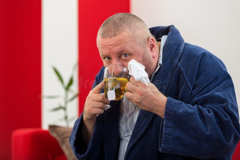 Άρρωστος άνδρας που φυσά τη μύτη του με την πετσέτα εγγράφου και που πίνει το τσάι στο σπίτι στοκ φωτογραφία