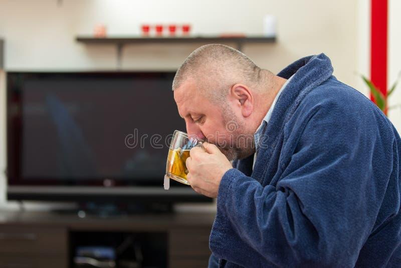 Άρρωστος άνδρας που φυσά τη μύτη του με την πετσέτα εγγράφου και που πίνει το τσάι στο σπίτι στοκ εικόνες με δικαίωμα ελεύθερης χρήσης
