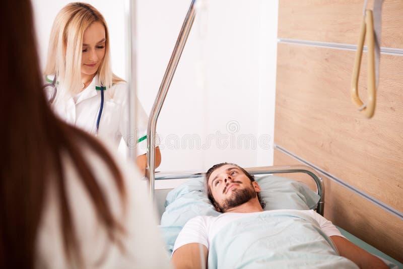 Άρρωστος αρσενικός ασθενής στο δωμάτιο νοσοκομείων δίπλα στις νοσοκόμες στοκ εικόνες με δικαίωμα ελεύθερης χρήσης