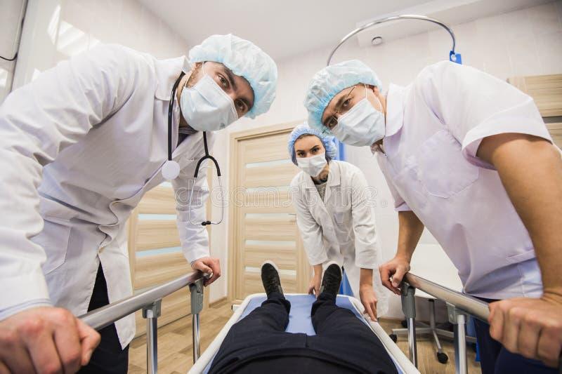 Άρρωστος ασθενής στο gurney στο λειτουργούν δωμάτιο με τους γιατρούς μπροστά από τον στοκ φωτογραφίες με δικαίωμα ελεύθερης χρήσης