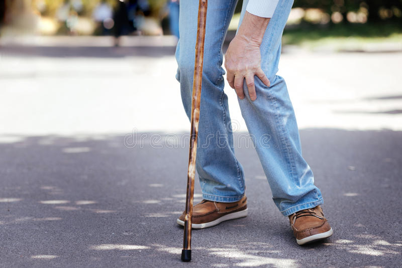 Άρρωστος ηλικίας άνδρας σχετικά με το ανεπαρκές γόνατο υπαίθρια στοκ εικόνες