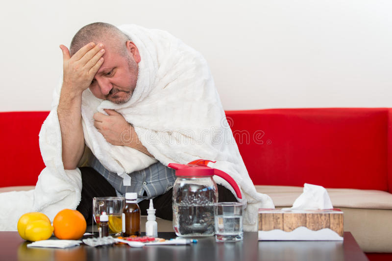 Άρρωστο άτομο που φορά την πυτζάμα που υφίσταται τον ιό γρίπης κρύου και χειμώνα που έχει την ιατρική στοκ εικόνες με δικαίωμα ελεύθερης χρήσης