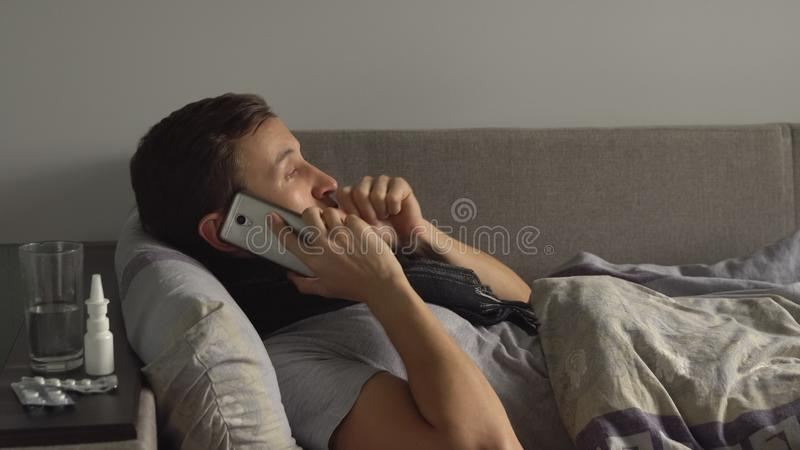 Άρρωστο άτομο στο κρεβάτι δίπλα στα φάρμακά του στο σπίτι του που μιλά στο τηλέφωνο Άτομο που υφίσταται τον ιό γρίπης κρύου και χ στοκ εικόνες