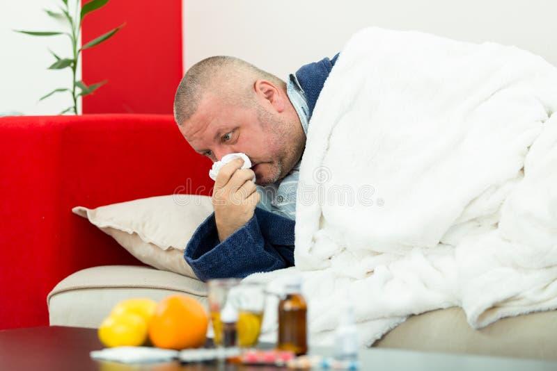 Άρρωστο άτομο στο κρεβάτι με τα φάρμακα και φρούτα στον πίνακα στοκ εικόνες