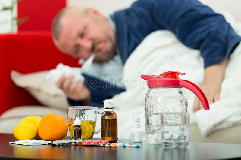 Άρρωστο άτομο στο κρεβάτι με τα φάρμακα και φρούτα στον πίνακα στοκ φωτογραφία με δικαίωμα ελεύθερης χρήσης