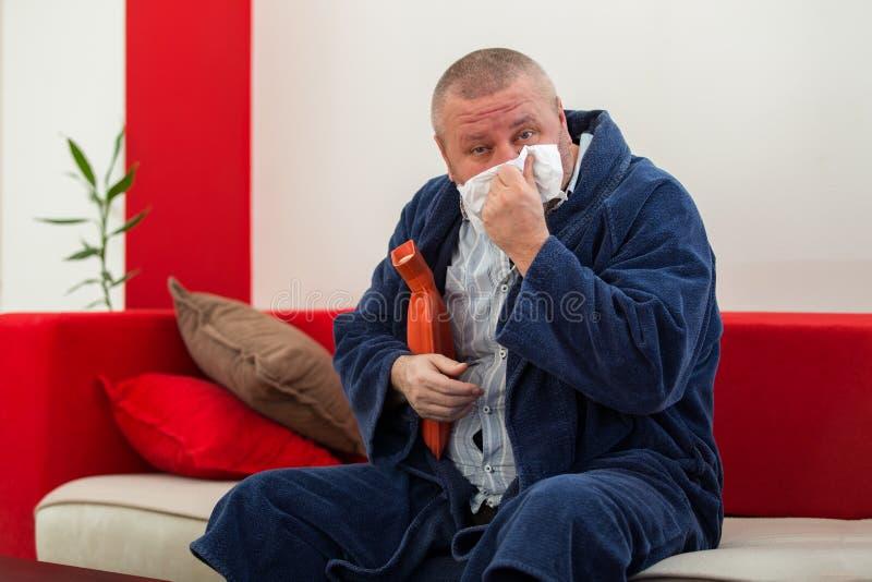 Άρρωστο άτομο στο κρεβάτι που έχει έναν πονοκέφαλο που κρατά ένα μπουκάλι ζεστού νερού στοκ εικόνα